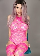 Bailey Jay in pretty pink behind gray background shows off as she strokes her hard massive dick
