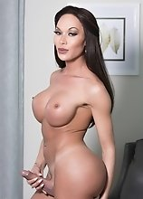 Mia Isabella sits on a leather sofa and plays with her huge throbbing juicy cock
